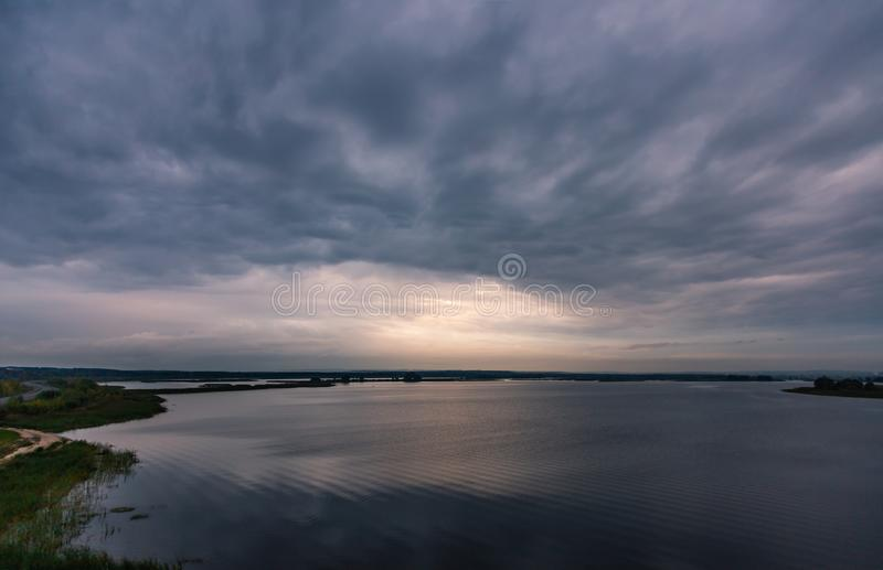 在日落的风雨如磐的多云天空在河伏尔加河 免版税库存照片