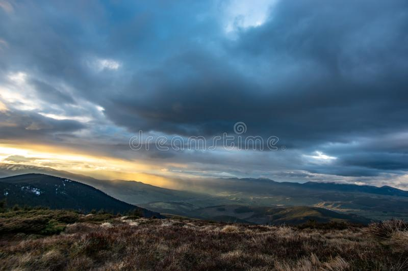 在日落的风雨如磐的天空在山 库存照片