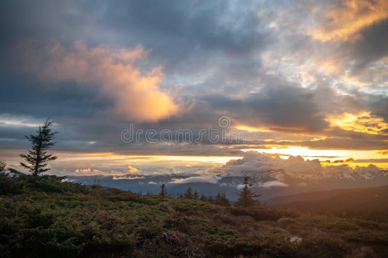 在日落的风雨如磐的天空在山 免版税库存图片