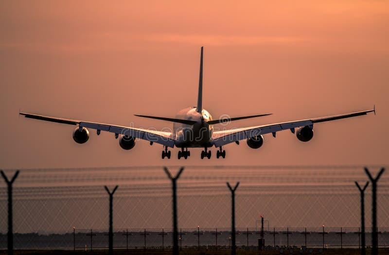 在日落的飞机着陆 免版税库存图片