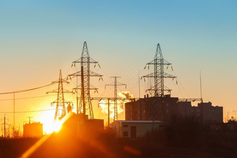 在日落的高压输电线 电发行驻地 免版税库存图片
