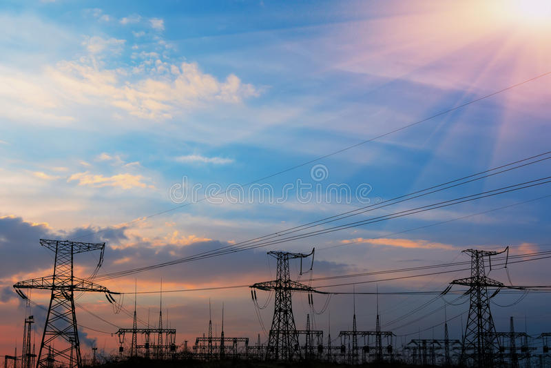 在日落的高压输电线 电发行驻地 高压电传输塔 免版税库存照片