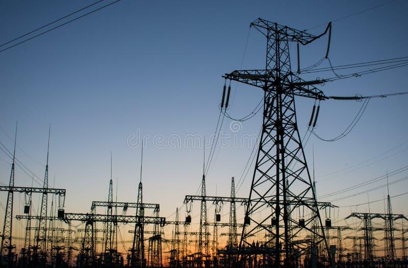 在日落的高压输电线 电发行sta 免版税库存图片