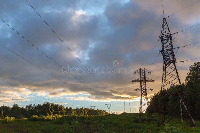 在日落的高压输电线 电发行sta 免版税库存照片