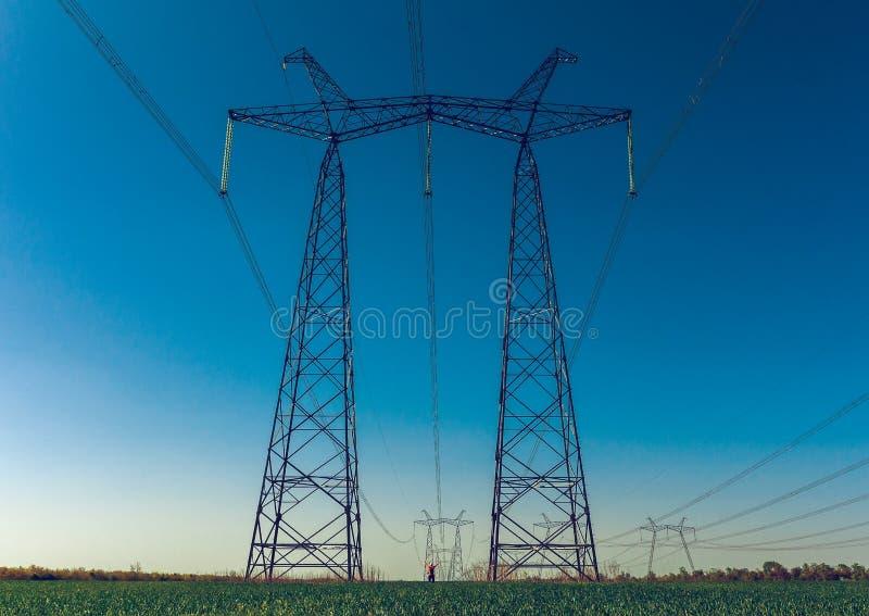 在日落的高压输电线 greeb领域 免版税库存图片