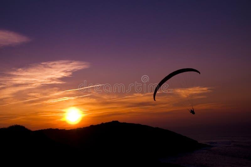 在日落的滑翔伞飞行 免版税库存图片