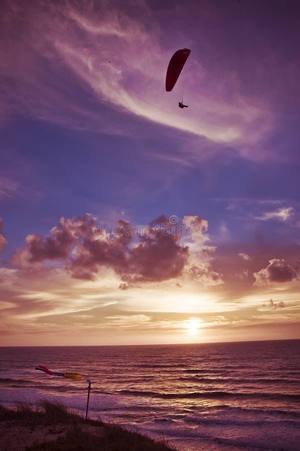 在日落的滑翔伞飞行 库存图片