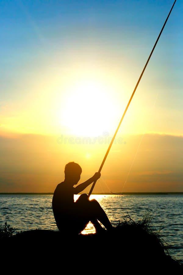 在日落的Fisher剪影 免版税库存照片