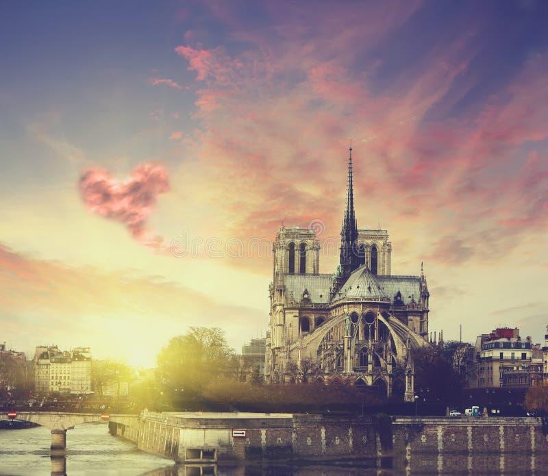 在日落的Notre Dame在巴黎,有云彩的法国以心脏的形式 库存照片