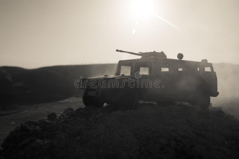 在日落背景的军用巡逻车 军队战争概念 装甲车剪影有枪的在行动 装饰 免版税图库摄影