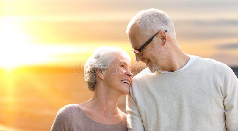 在日落背景的愉快的资深夫妇 免版税库存照片