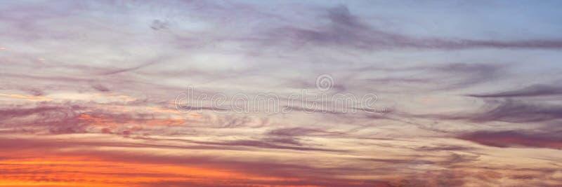 在日落被点燃的天空,看起来象绘的宽横幅背景的橙色和蓝色云彩 库存照片
