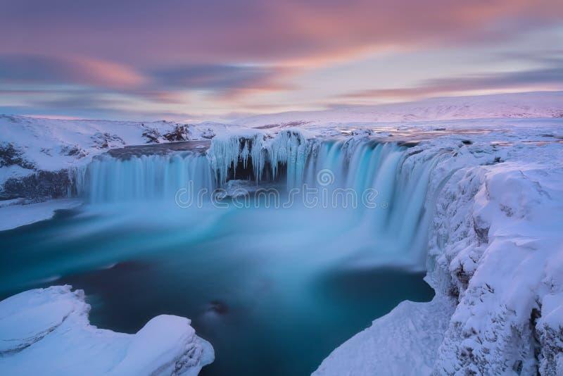 在日落视图的Godafoss瀑布在冰岛,北欧附近在与最强有力的瀑布的雪和冰一的冬天 库存图片