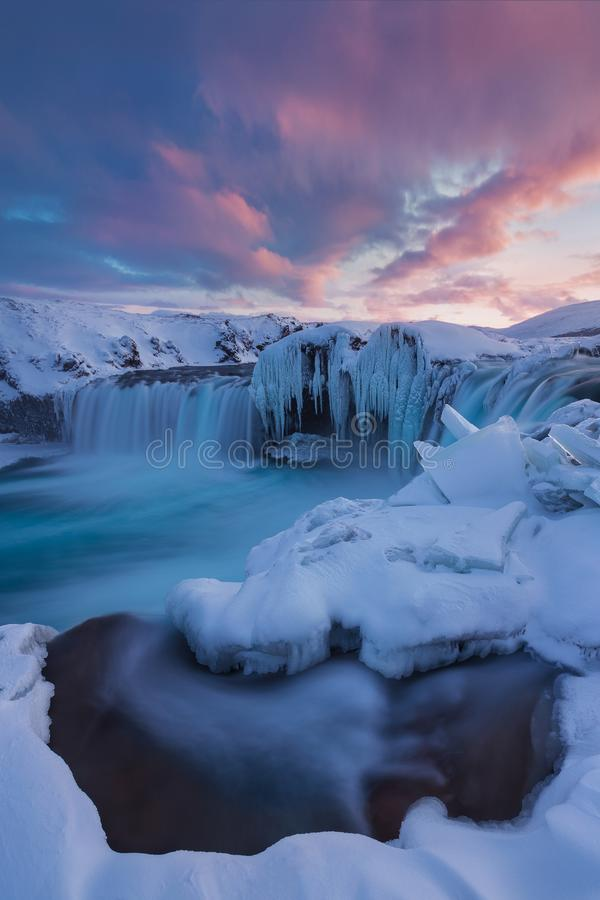 在日落视图的Godafoss瀑布在冰岛,北欧附近在与最强有力的瀑布的雪和冰一的冬天 免版税库存照片