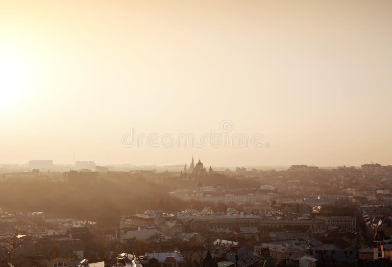 在日落,乌克兰的利沃夫州市有薄雾的风景 库存图片
