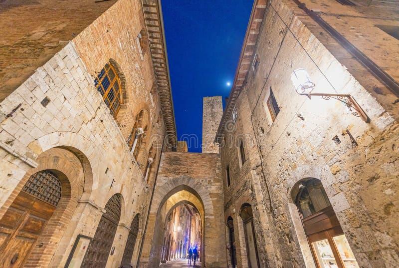在日落,托斯卡纳-意大利的圣吉米尼亚诺建筑学 免版税库存照片