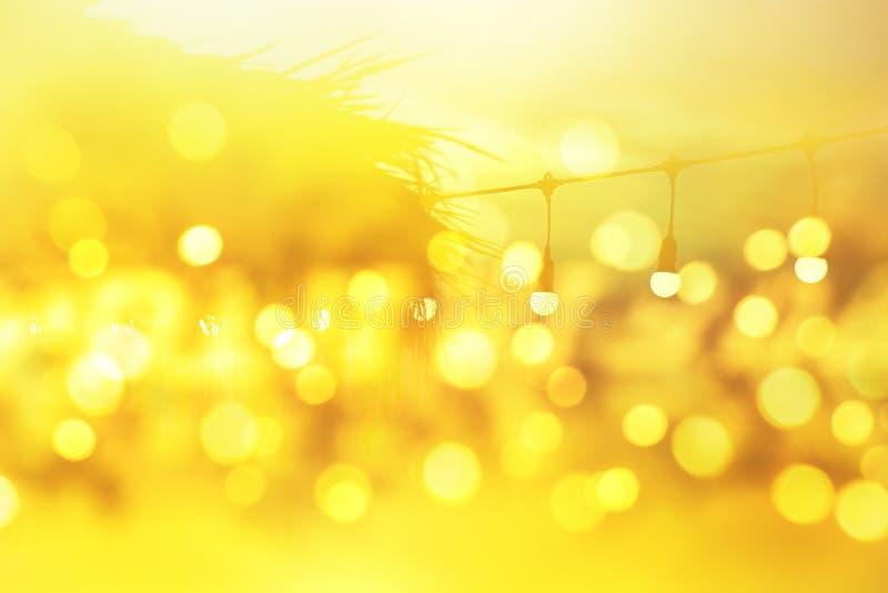 在日落,黄色串光的被弄脏的轻的bokeh在室外餐馆,抽象背景 图库摄影