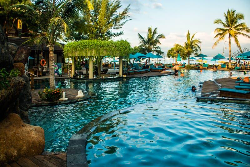 在日落, Gili Trawangan,龙目岛,印度尼西亚期间,在热带手段的游泳池附近使sunbeds靠岸与棕榈 库存图片