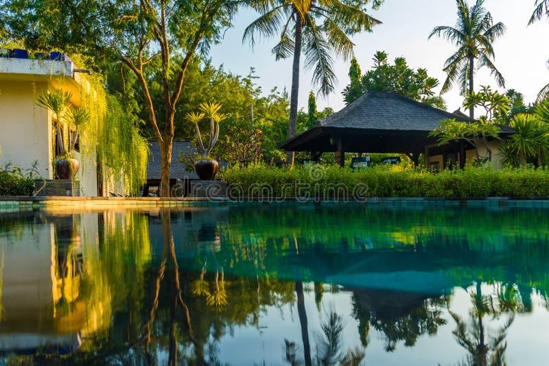 在日落, Gili Trawangan,龙目岛,印度尼西亚期间,在热带手段的游泳池附近使sunbeds靠岸与棕榈 免版税库存图片