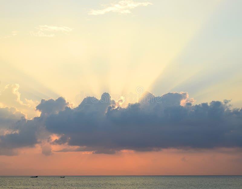 在日落-传播通过与橙色天空的云彩的黄昏明亮的阳光的时期的Skyscape在蓝色海水的天际 库存图片