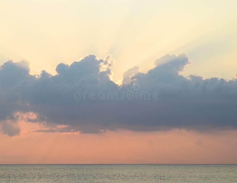 在日落-传播通过与橙色天空的云彩的黄昏明亮的阳光的时期的Skyscape在蓝色海水的天际 库存照片