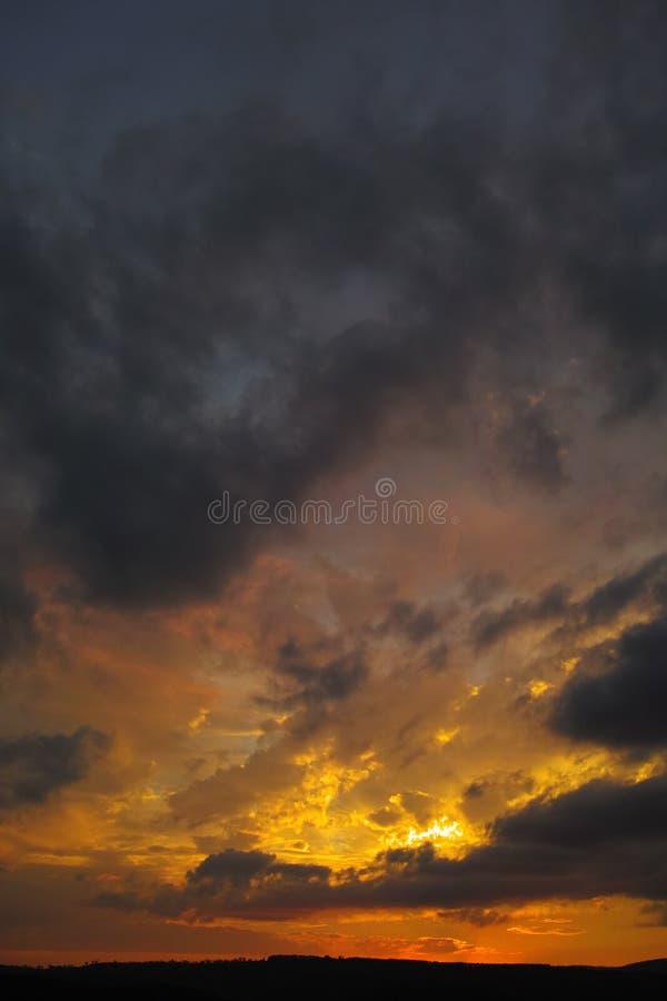 在日落以后的剧烈的多云暮色天空与橙红颜色 免版税库存照片