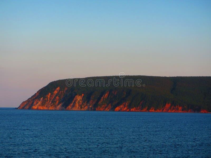 在日落Ingonish海滩新斯科舍的海边峭壁 库存图片