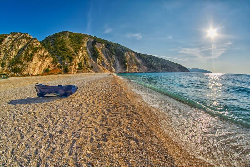 在日落Myrtos海滩的老被放弃的渔夫小船在Kefalonia,希腊 免版税图库摄影