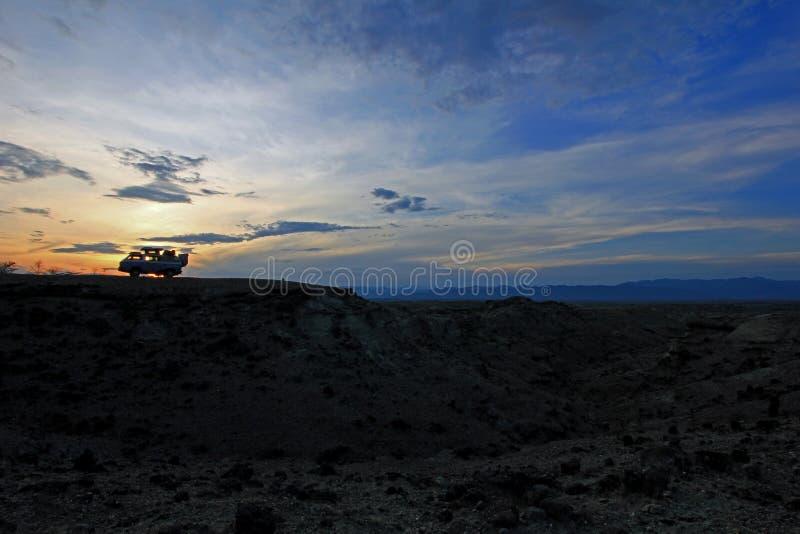 在日落tatacoa沙漠的露营者货车 库存图片