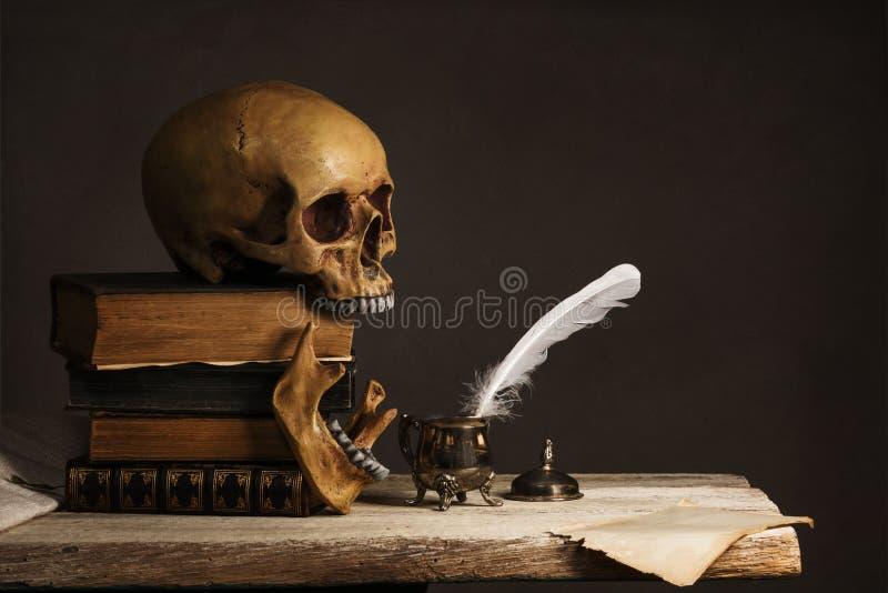 在旧书的人的头骨与空的页、羽毛和墨水瓶 免版税库存图片