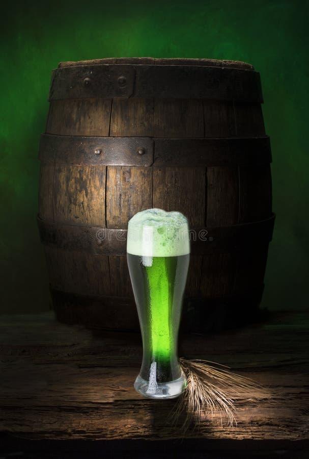 在旧木桶上喝着绿色啤酒 免版税库存照片