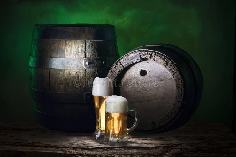 在旧木桶上喝着绿色啤酒 库存图片