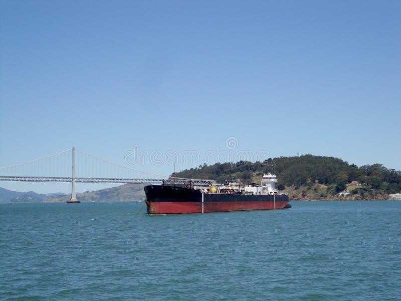 在旧金山湾桥梁和海岛前面的货船 库存图片
