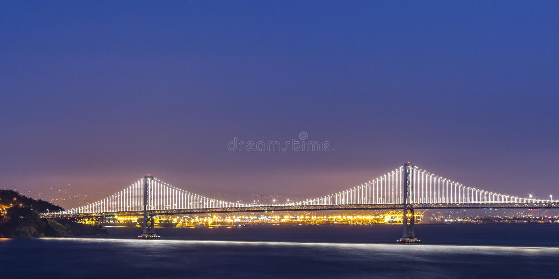 在旧金山湾的发光的海湾桥梁在晚上 库存照片