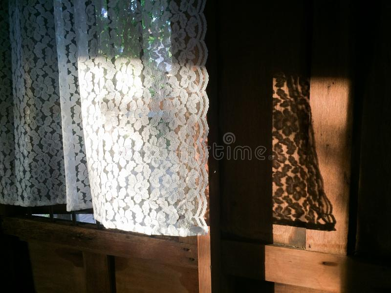 在早晨光、窗口、阴影和老木背景的美丽的白色帷幕 泰国的房子 温暖的口气 背景,纹理 库存图片