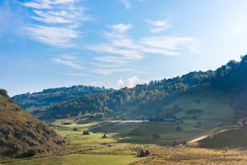 在早晨光的美好的农村山风景与老房子和干草堆 免版税库存照片