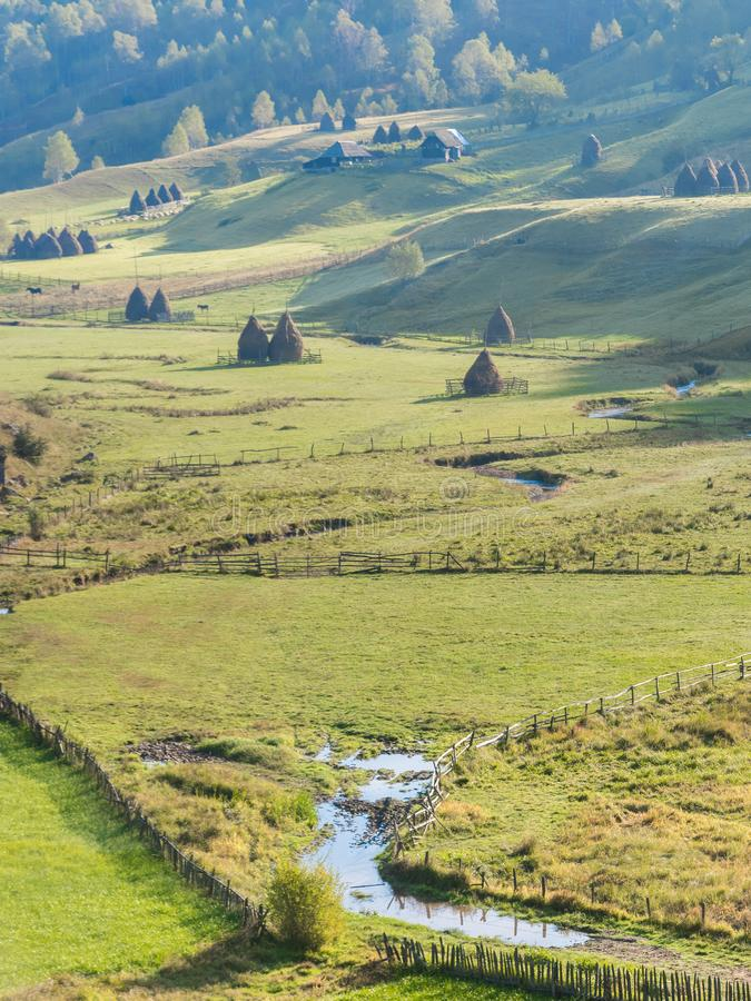 在早晨光的美好的农村山风景与老房子和干草堆 库存图片
