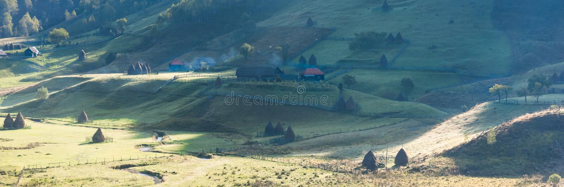 在早晨光的美好的农村山风景与老房子和干草堆 库存照片