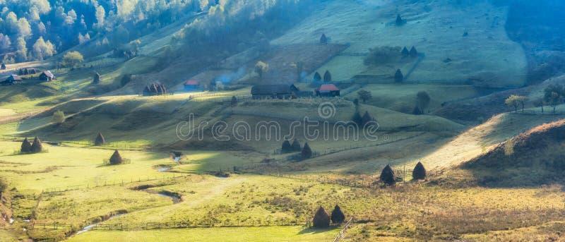 在早晨光的美好的农村山风景与老房子和干草堆 免版税库存图片