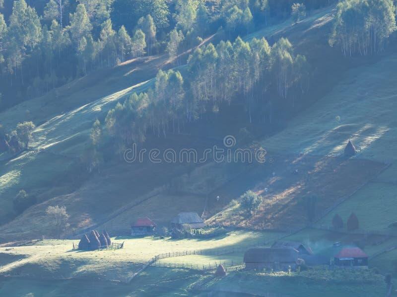 在早晨光的美好的农村山风景与雾、老房子和干草堆 图库摄影