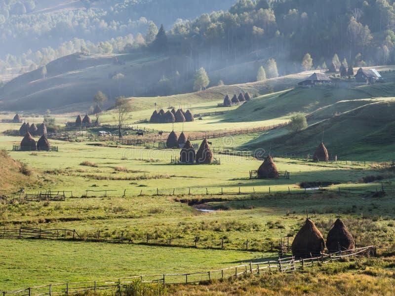 在早晨光的美好的农村山风景与雾、老房子和干草堆 库存图片