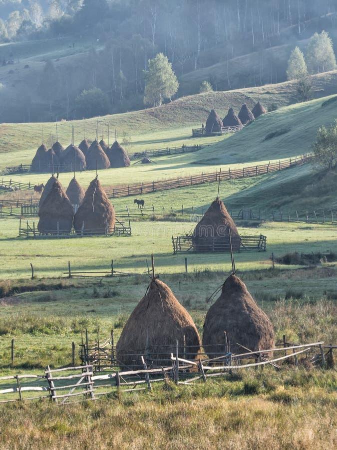 在早晨光的美好的农村山风景与雾、老房子和干草堆 免版税图库摄影