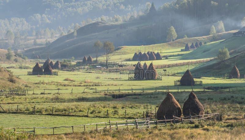 在早晨光的美好的农村山风景与雾、老房子和干草堆 库存照片
