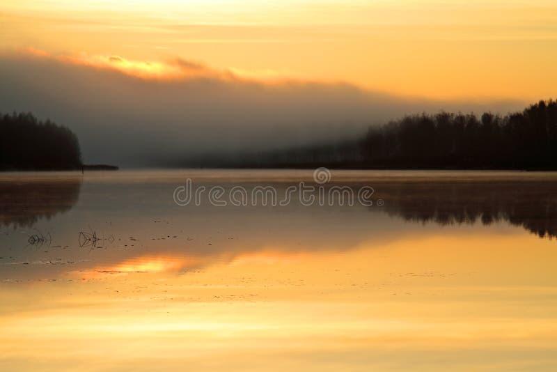 在早晨太阳上升的有雾的湖岸 免版税库存照片