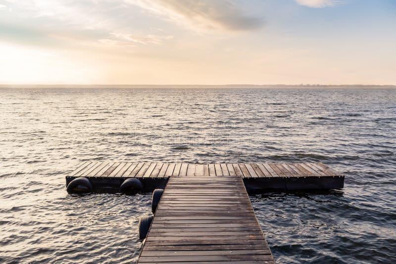 在早晨太阳的平安的空的木桥 免版税库存图片