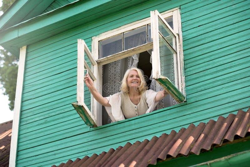 在早晨早晨醒的资深白肤金发的妇女开窗口 免版税图库摄影
