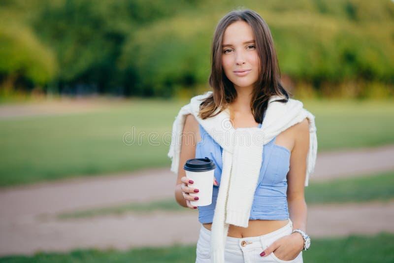 在早晨期间,在偶然T恤杉穿戴的深色的妇女室外射击,白色长裤,在口袋保留手,喝芳香咖啡 库存照片