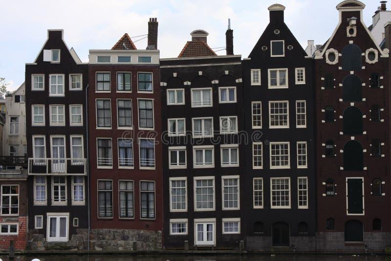 在早晨蓝色小时,有典型的荷兰房子和居住船的,荷兰,荷兰阿姆斯特丹运河Singel 半新定调子 免版税库存图片