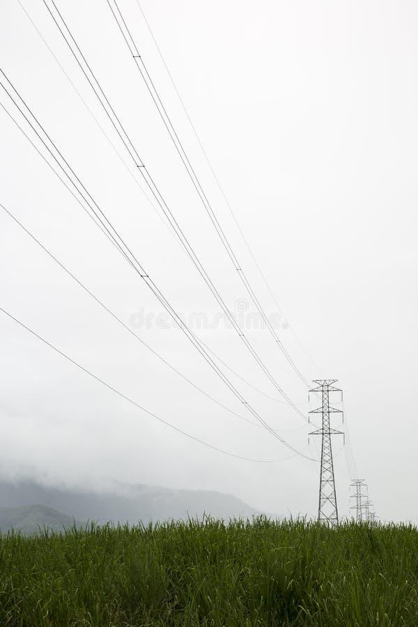 在早晨薄雾的送电线 免版税库存图片