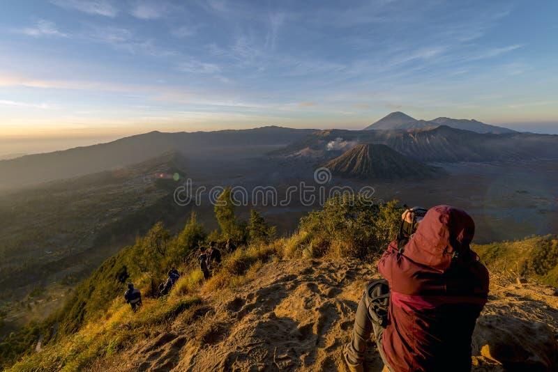 在早期的mornin期间,远足者敬佩布罗莫火山壮观的看法  免版税库存照片